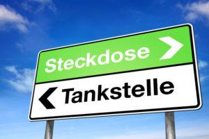Wegweiser mit Steckdose und Tankstelle: Welchen Weg gehen wir bei den Antriebstechniken?